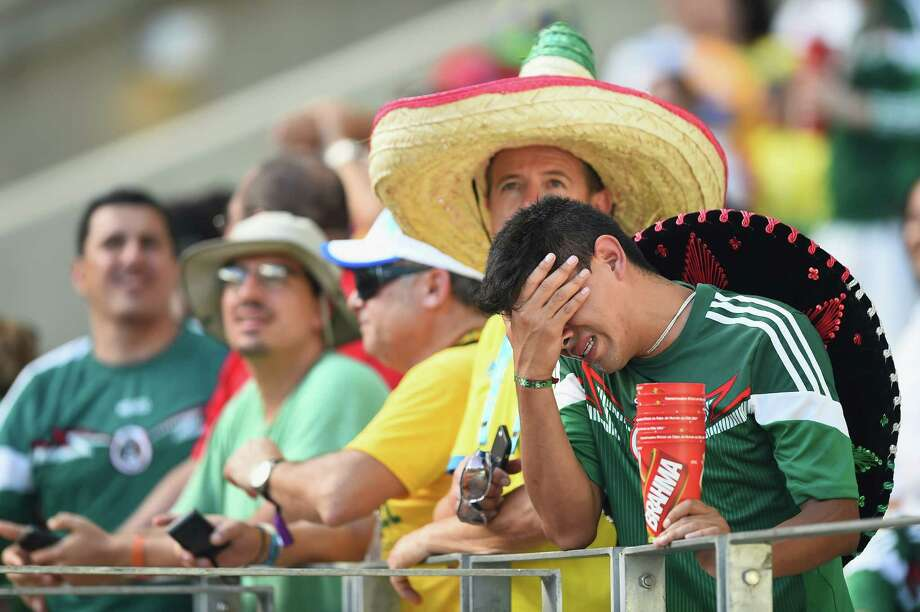 A fan of Mexico in Fortaleza, Brazil, shows his despair over the outcome of the match, in which Mexico fell 2-1 to the Netherlands. Photo: Laurence Griffiths, Staff / 2014 Getty Images