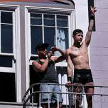 Two men hang out on the fire escape of an apartment building along Hyde Street near Turk as people party it up in the streets below at the 44th annual San Francisco Gay Pride Parade in San Francisco, Calif. on Sunday, June 29, 2014.