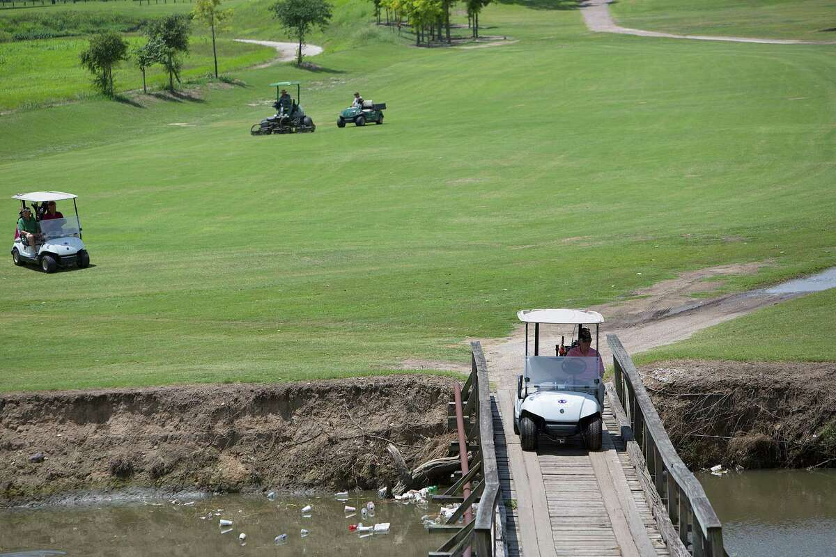 Golfers ride to the green over a waterway full of garbage on the seventh hole at Gus Wortham Golf Course on Tuesday.