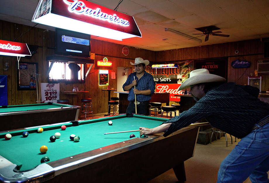 Ray Runnels, right, and his son, Ray Runnels Jr., play a game of pool Thursday at Swett Tavern. Photo: Eric Ginnard, MBR / Rapid City Journal