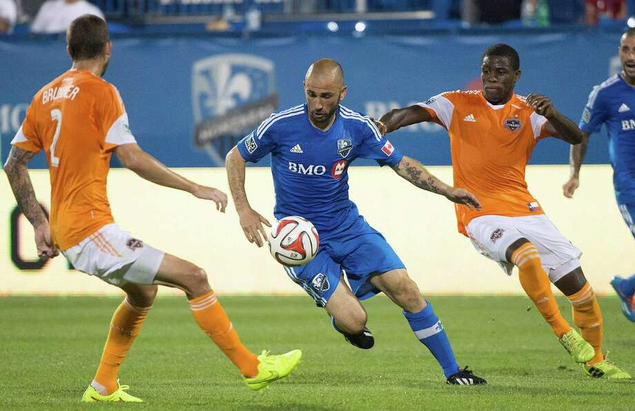 Montreal Impact's Marco Di Vaio, center, moves the ball by Houston Dynamo's Eric Brunner, left, and Kofi Sarkodie during the second half of an MLS soccer game in Montreal, Sunday, June 29, 2014. (AP Photo/The Canadian Press, Graham Hughes) Photo: Graham Hughes, Associated Press / The Canadian Press
