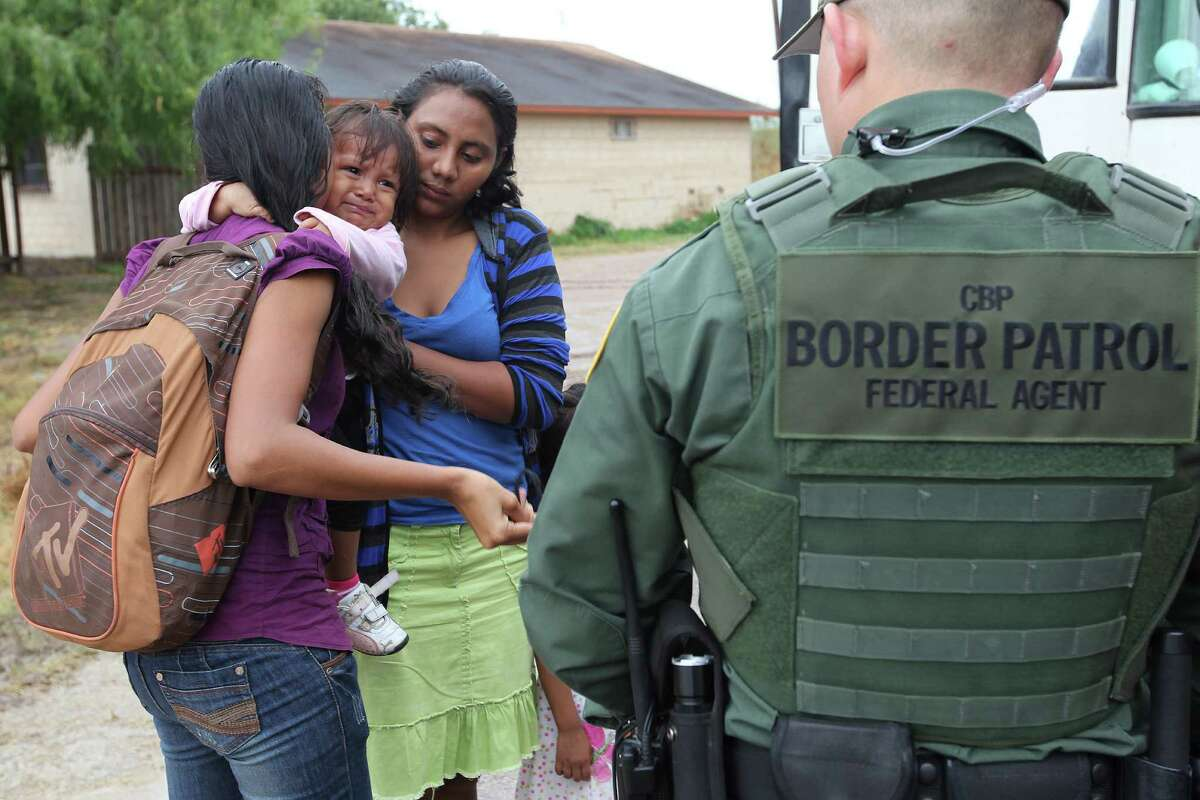 U.S. Border Patrol agents process a group of immigrants in Granjeno. The city is just north of a hotbed of illegal border crossing on the Rio Grande by juveniles and mothers with children.