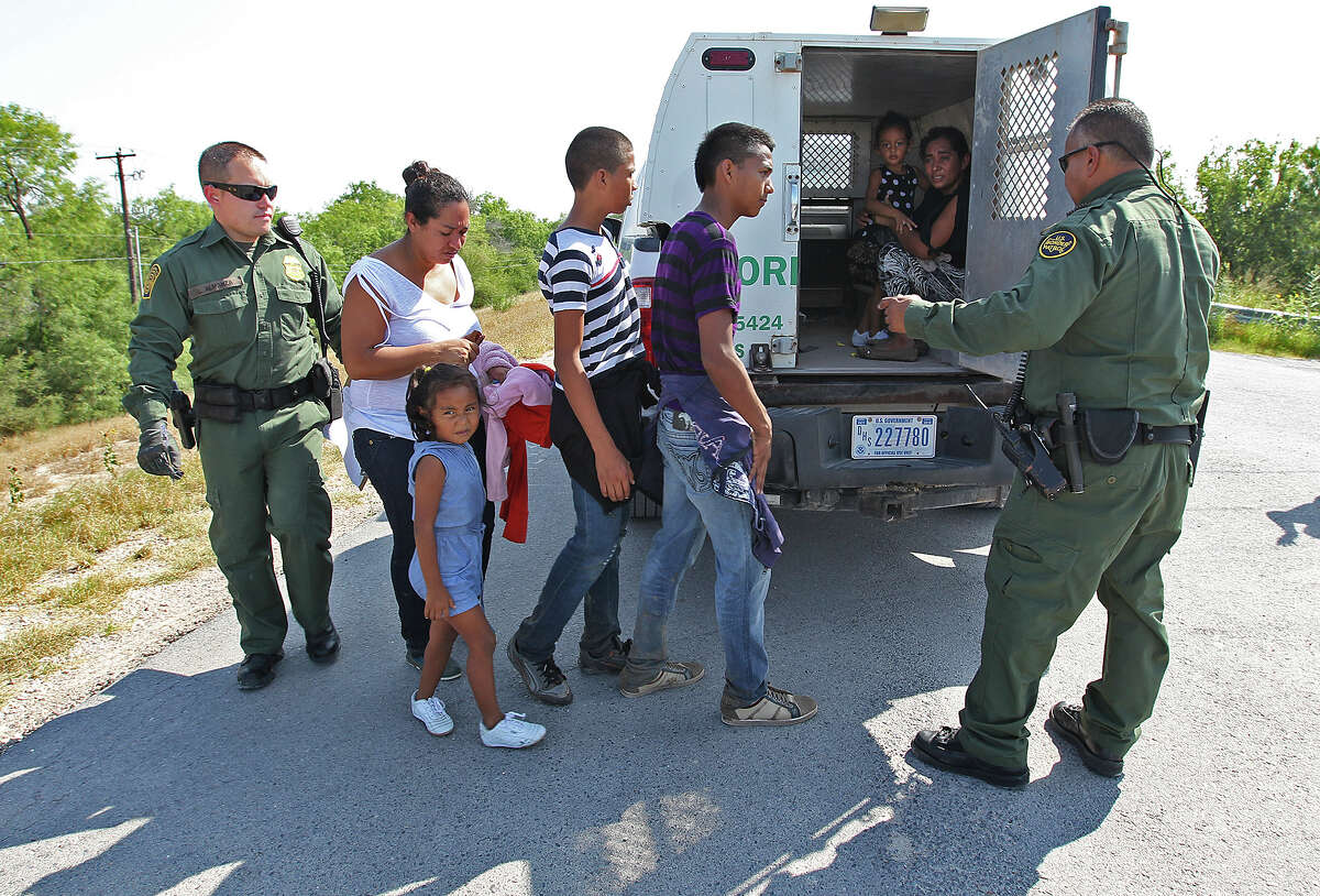U.S. Border Patrol agents load a group of immigrants onto a van near Anzalduas Park, southwest of McAllen, on Wednesday. In Hidalgo County, about 1,000 immigrants per day are turning themselves in to the Border Patrol.