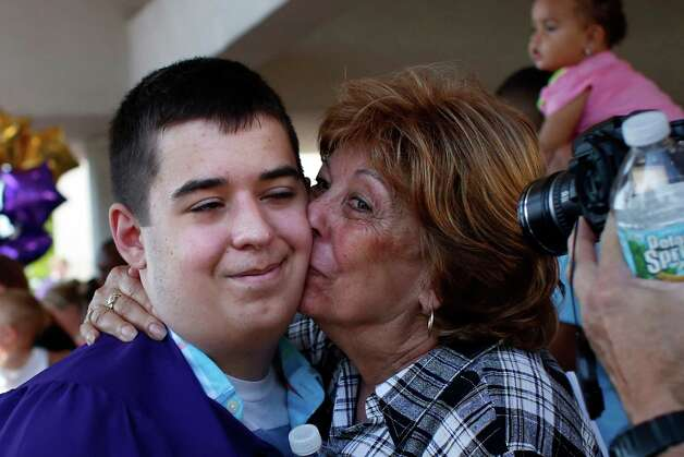 Troy high school graduate Nicholas Cipriani, center, receives a kiss from his grandmother, Suzann, following graduation commencement at Hudson Valley Community College on Sunday, June 29, 2014, in Troy, N.Y.  (Tom Brenner/ Special to the Times Union) Photo: Tom Brenner / ©Tom Brenner/ Albany Times Union