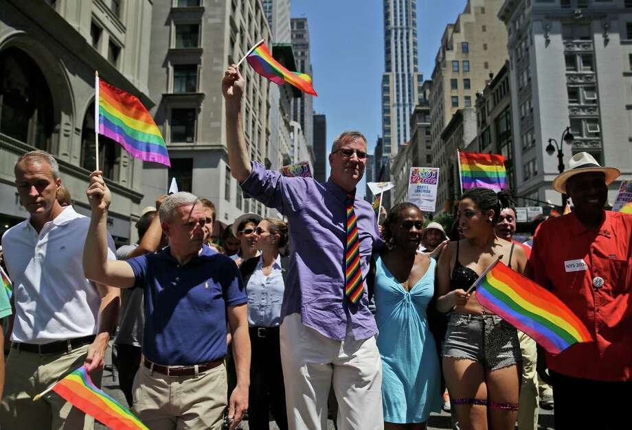 New York CityNew York City Mayor Bill de Blasio, center, marches in the Gay Pride Parade in New York, Sunday, June 29, 2014. Fifth Avenue became one big rainbow on Sunday, as thousands of participants waving multicolored flags made their way down the street for New York City's annual Gay Pride march. (AP Photo/Seth Wenig) ORG XMIT: NYSW104 Photo: Seth Wenig / AP