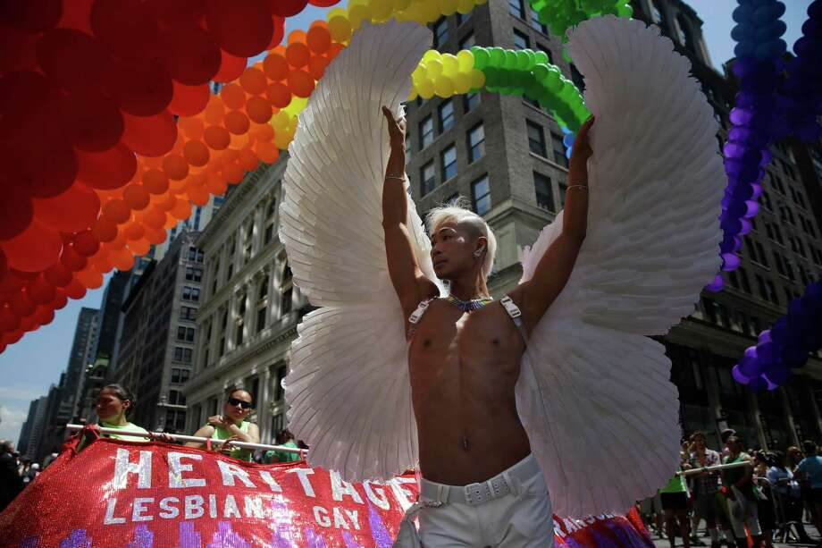 New York CityKent Chua poses for pictures at the start of the Gay Pride Parade in New York, Sunday, June 29, 2014. Fifth Avenue became one big rainbow on Sunday, as thousands of participants waving multicolored flags made their way down the street for New York City's annual Gay Pride march. (AP Photo/Seth Wenig) ORG XMIT: NYSW103 Photo: Seth Wenig / AP