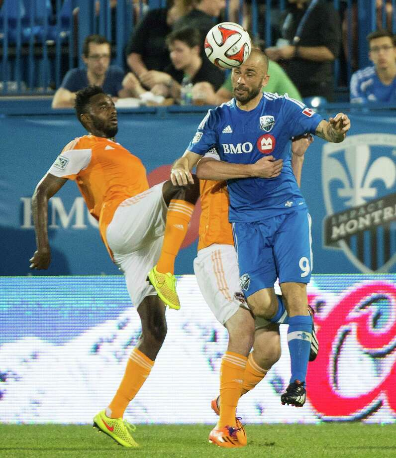 Montreal's Marco Di Vaio battles Warren Creavalle, left, and another Dynamo. Photo: Graham Hughes, SUB / The Canadian Press