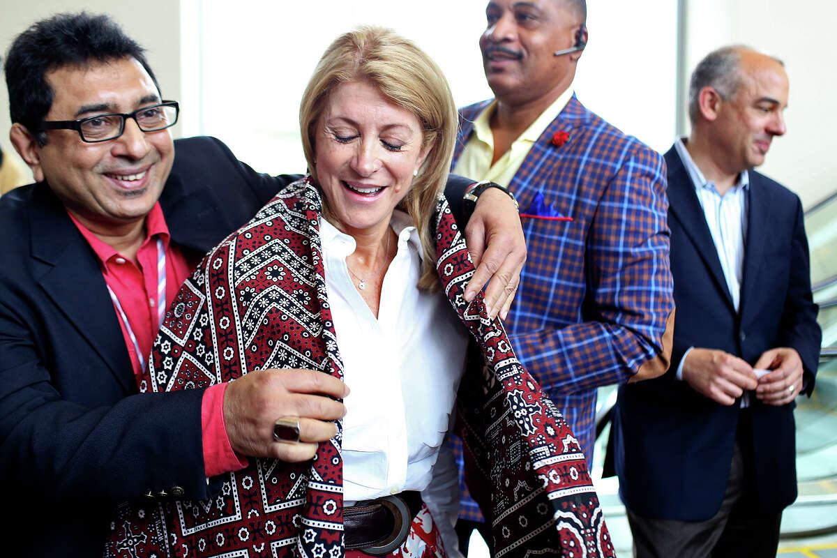 State Senator and candidate for Governor Wendy Davis is presented with an Ajrak, a shawl from the Sindh province of Pakistan, by Raja Zahid Khanzada, left, with the Muslim Democratic Caucus of Texas, during the Texas Democratic State Convention at the Dallas Convention Center in Dallas on Saturday, June 28, 2014.