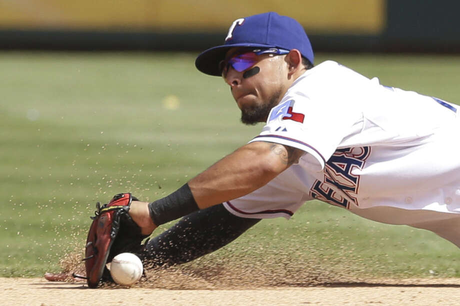 Rangers shortstop Elvis Andrus dives for a ground ball hit by the Twins' Joe Mauer in the eighth. Photo: LM Otero / Associated Press / AP
