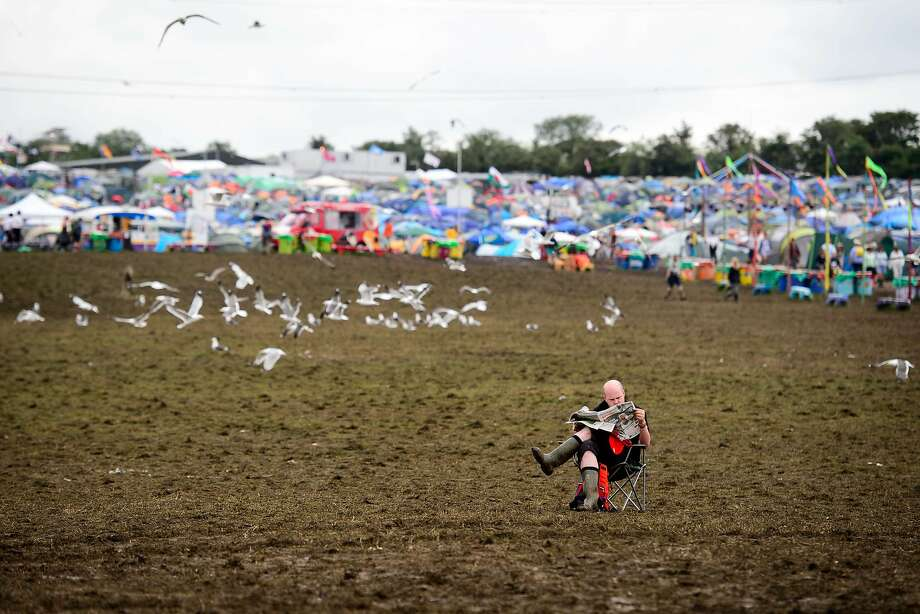 A man reads his Sunday newspaper as revellers wake on the last day of the Glastonbury Festival of Music and Performing Arts in Somerset, southwest England, on June 29, 2014. AFP PHOTO / LEON NEALLEON NEAL/AFP/Getty Images Photo: Leon Neal, AFP/Getty Images
