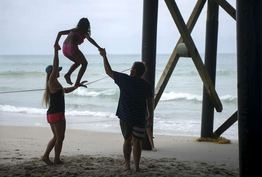 Alex Bozeman, 24, of San Clements, left, and Stavros Polopulus, 24, of Capistrano Beach, Calif., help Malia Mayo, 9, walk along a slackline underneath the San Clemente, Calif., Pier June 29, 2014.   (AP Photo/The Orange County Register,Matt Masin)   MAGS OUT; LOS ANGELES TIMES OUT Photo: Matt Masin, Associated Press