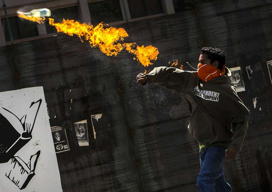 A protester throws a molotov cocktail at Bolivarian National Police during a protest against the government of President Nicolas Maduro in Caracas, Venezuela, Tuesday, June 24, 2014. University students and government opponents protested in the east of the capital and demanded the release of people who have been arrested in street demonstrations in recent months. (AP Photo/Ramon Espinosa) Photo: Ramon Espinosa, Associated Press