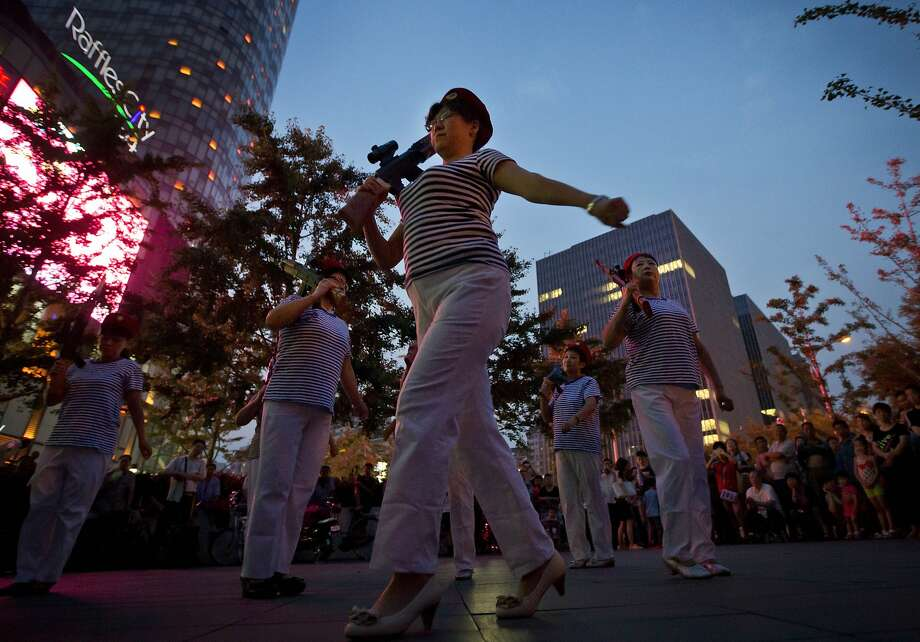 Chinese women holding toy guns dance to a revolutionary song during their daily exercises at a square outside a shopping mall in Beijing, China Sunday, June 29, 2014. Local residents in the capital city frequently gather at public squares or parks to  perform  their daily fitness activities. (AP Photo/Andy Wong) Photo: Andy Wong, Associated Press