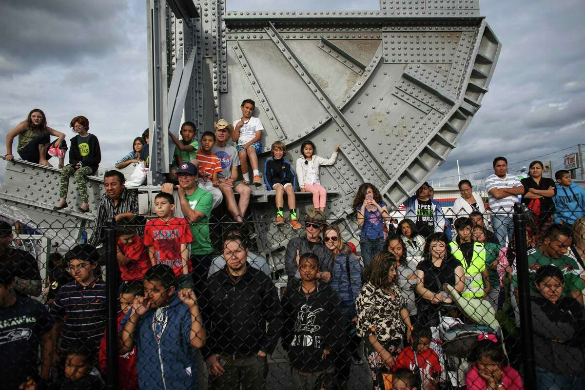 People sit on a decorative piece of the old bridge as they watch Lucha Libre wrestling during a celebration of the completion of the new South Park Bridge over the Duwamish River. The event featured a parade, many speeches by politicians and community leaders, music, dancing and of course Lucha Libre wrestling.