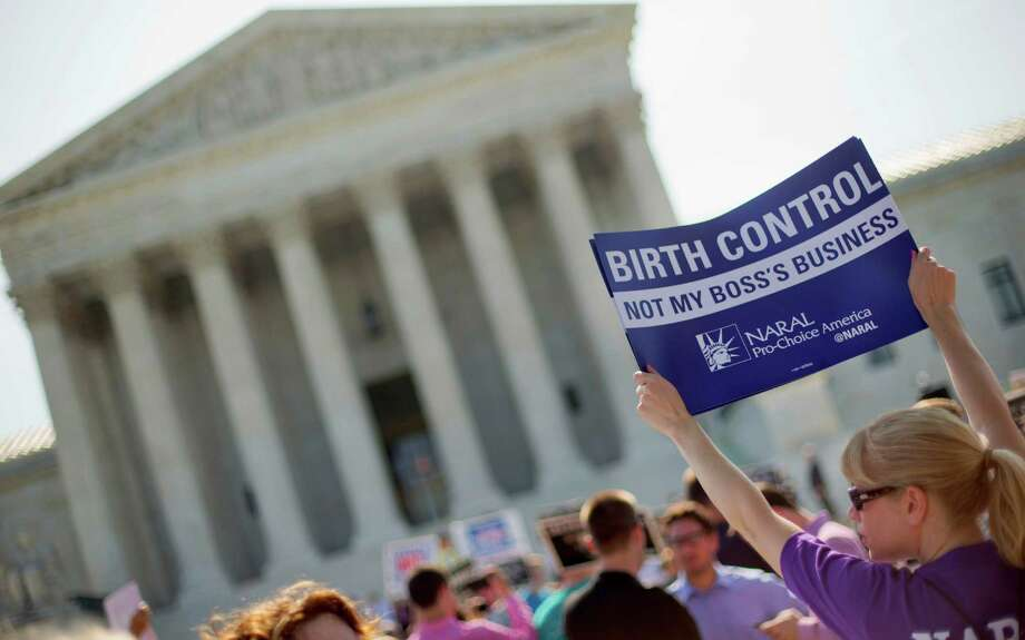 A demonstrator holds up a sign outside the Supreme Court in Washington, Monday, June 30, 2014. The Supreme Court is poised to deliver its verdict in a case that weighs the religious rights of employers and the right of women to the birth control of their choice. Photo: Pablo Martinez Monsivais, AP / AP