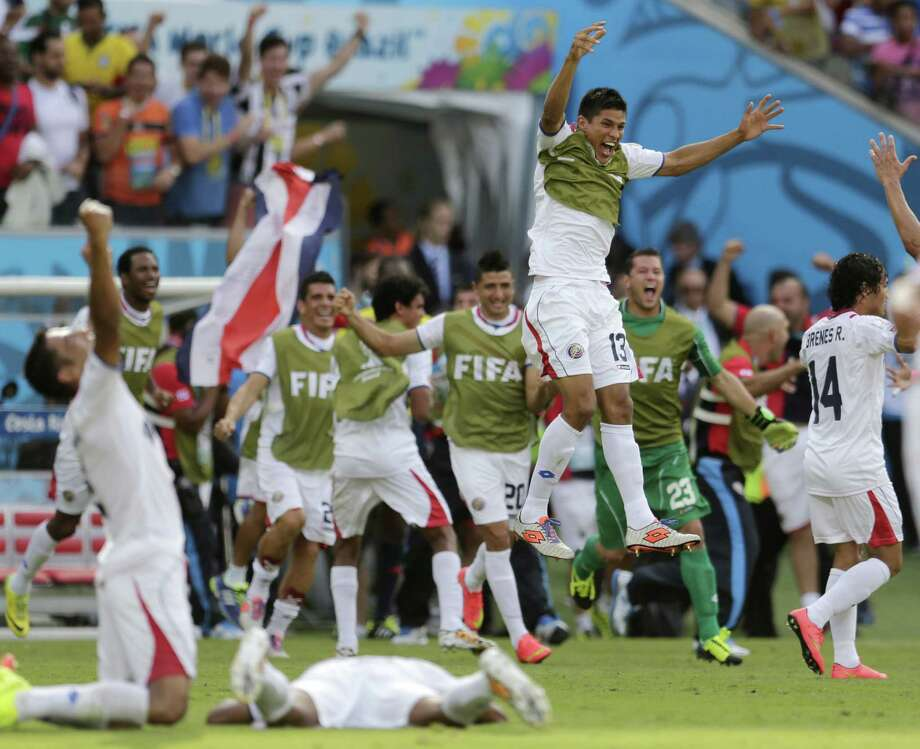 Costa Rican players come off their bench to celebrate their victory over Italy in their  World Cup soccer match. Costa Rica also surprised Uruguay with a 3-1 win. Photo: Petr David Josek / Associated Press / AP