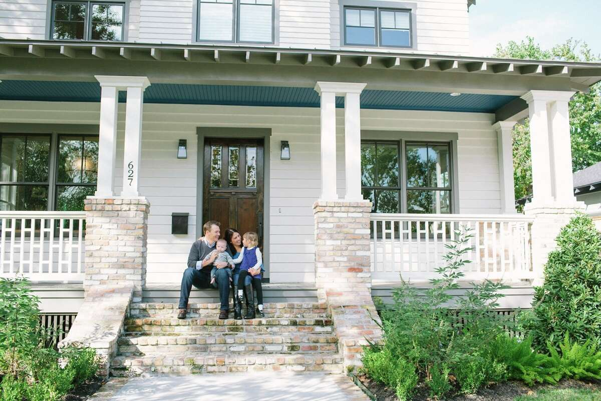 Jason and Nicole Vogler pose with their kids on the front porch of their Heights home.