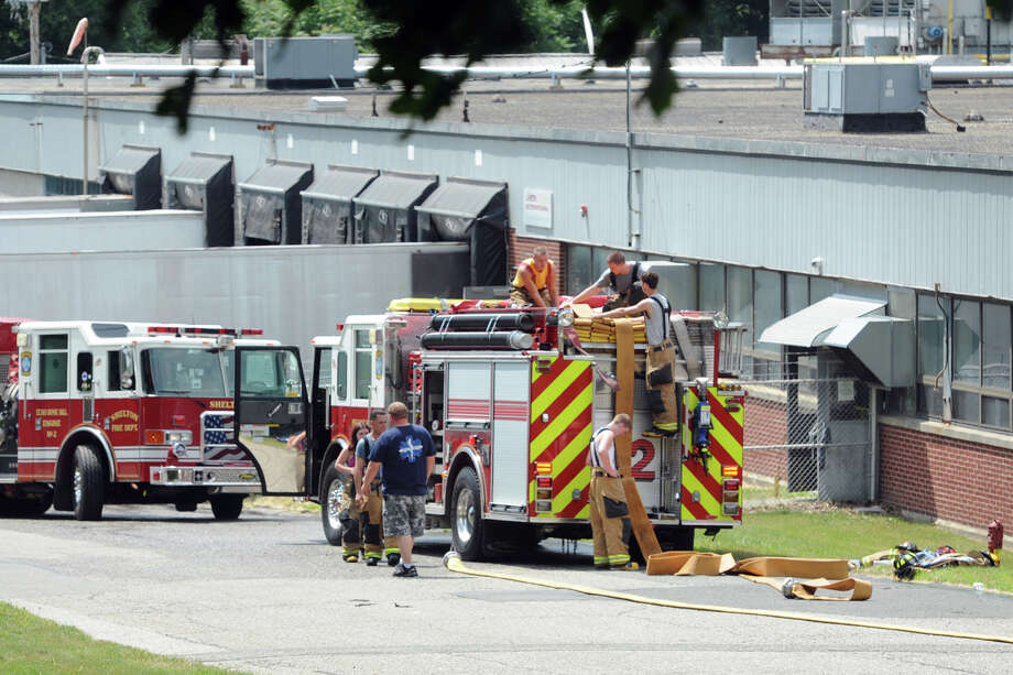 Firefighters clean up after responding to a call at Latex International, in Shelton, Conn. June 30, 2014. Photo: Ned Gerard / Connecticut Post