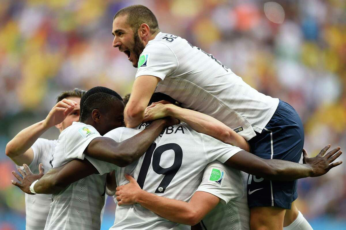 TOPSHOTS France's midfielder Paul Pogba (C, hidden) celebrates with France's forward Karim Benzema (top) and other teammates after scoring the first goal during a Round of 16 football match between France and Nigeria at Mane Garrincha National Stadium in Brasilia during the 2014 FIFA World Cup on June 30, 2014. AFP PHOTO / FABRICE COFFRINIFABRICE COFFRINI/AFP/Getty Images