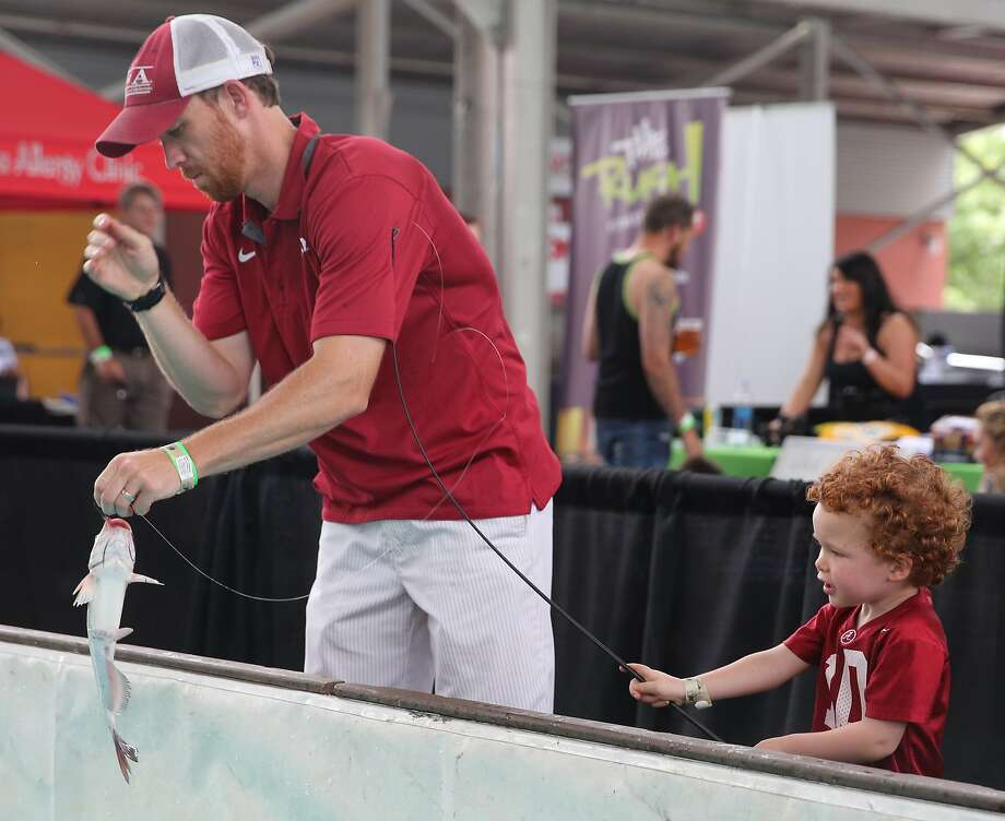 Is it a keeper, Dad? Shane Wright pulls a hook out of the mouth of a fish that he and his 3-year-old 