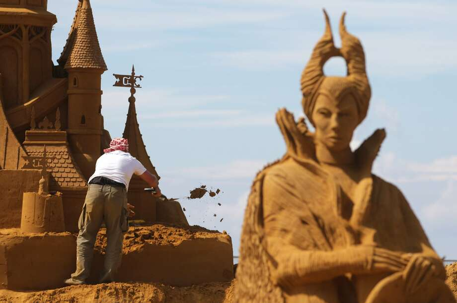 Castle construction:An artist works on his creation at a sand sculpture festival in the North Sea town of Ostend,   Belgium. The theme of the fest was Disneyland. Photo: Yves Logghe, Associated Press