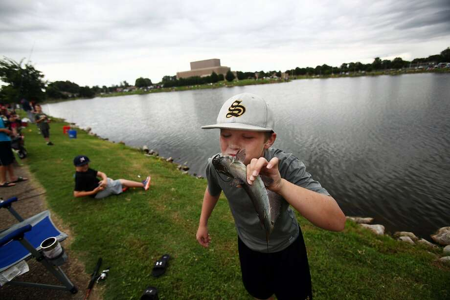 Oh, you beautiful bottom-feeder: Eight-year-old Carter McKay kisses a catfish he caught during   the City of Bartlett, Tenn.'s Children's Fishing Rodeo at Appling Lake. Photo: Kyle Kurlick, Associated Press