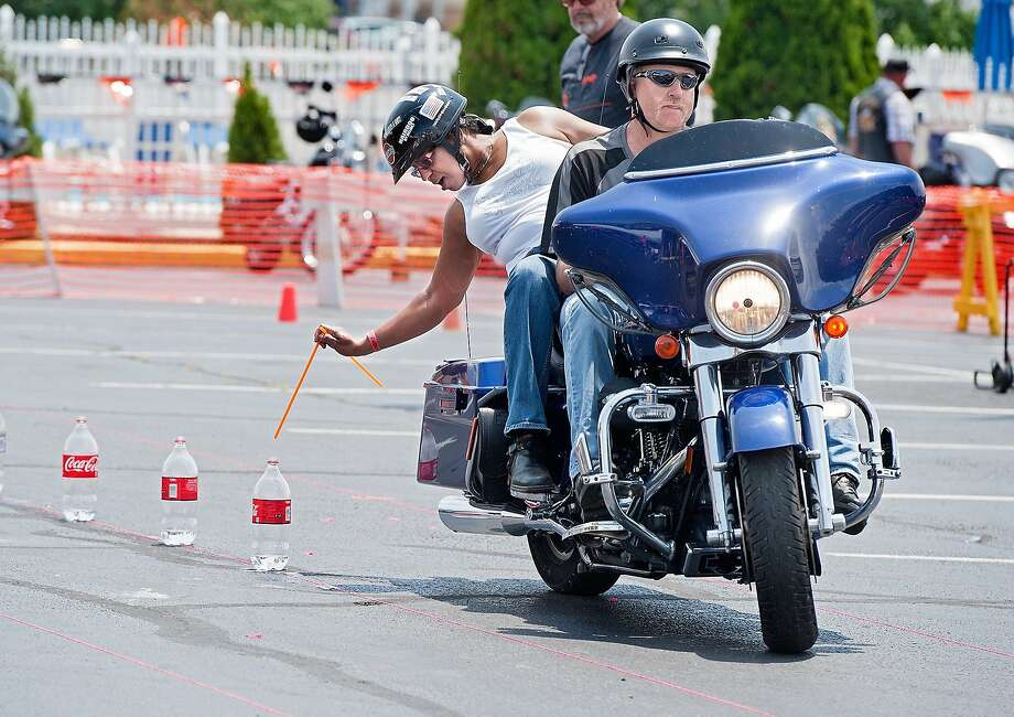 Harley couple:Colleen Simpson tries to drop a straw in a Coke bottle as her husband, Roger, 