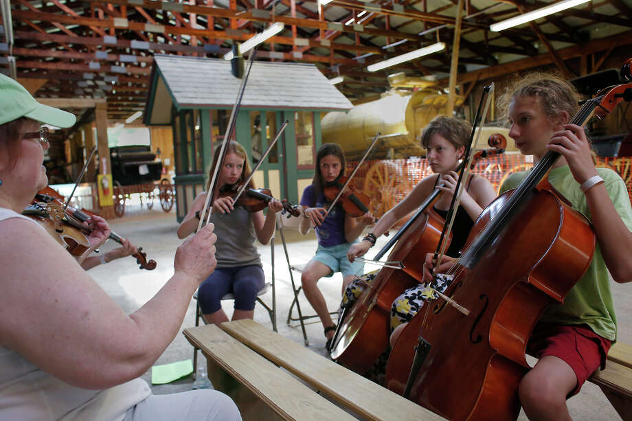 Donna Hebert, left, of the Great Groove Band, teaches children how to play fiddle, violin and cello at the Old Songs Festival at the Altamont Fairgrounds on Friday, June 27, 2014, in Altamont, N.Y.  The music festival runs through Sunday. (Tom Brenner/ Special to the Times Union) Photo: Tom Brenner / ©Tom Brenner/ Albany Times Union