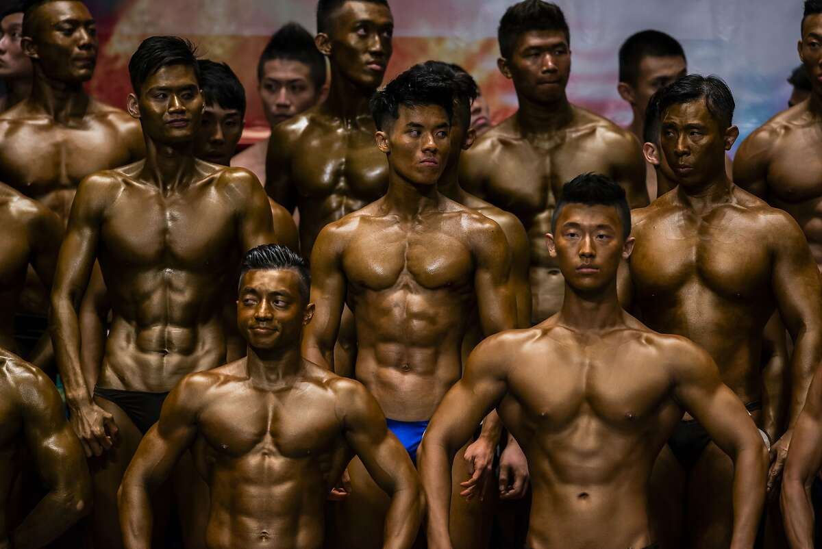 My abs are better than your abs: Bodybuilders with painted tans flex for judges on stage during the Hong Kong Bodybuilding Championship .
