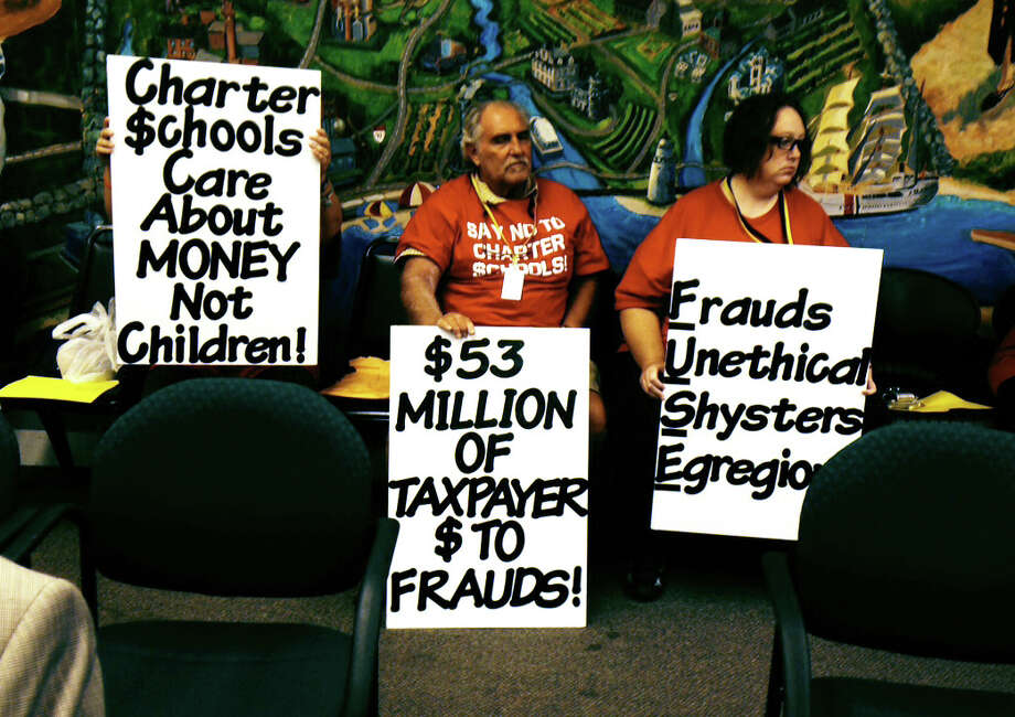 Bridgeport residents hold signs in the back row at a special state Board of Education meeting in Hartford convened to hire a special investigator to probe the management firm that runs Dunbar School and at least three other state charter schools. Photo: Linda Connor Lambeck / Connecticut Post