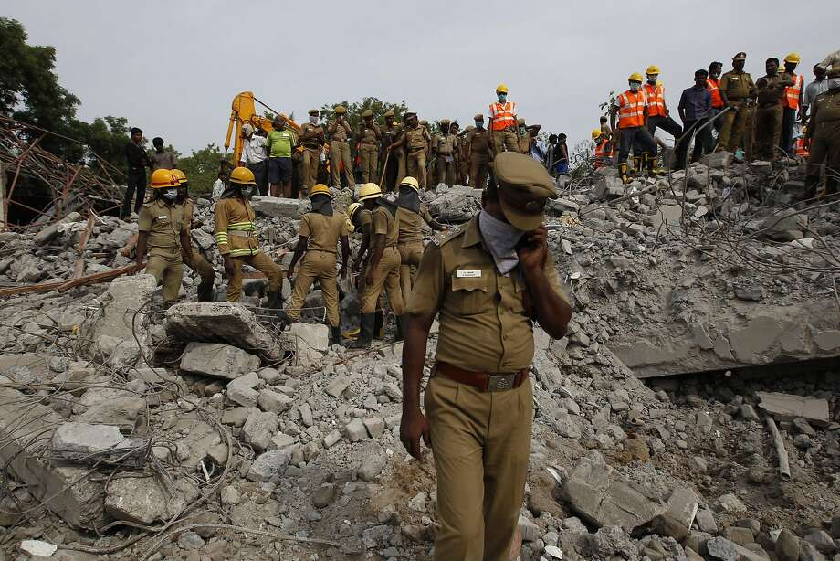 Rescuers search for workers from the building that collapsed late Saturday during monsoon rains. Photo: Arun Sankar K, Associated Press