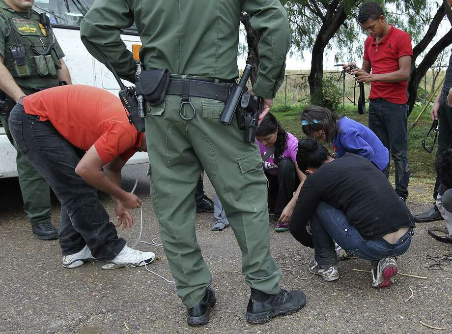 U.S. Border Patrol agents detain immigrants in Granjeno. A surge of unaccompanied minors is causing political headaches. Photo: Jerry Lara / San Antonio Express-News / ©2014 San Antonio Express-News