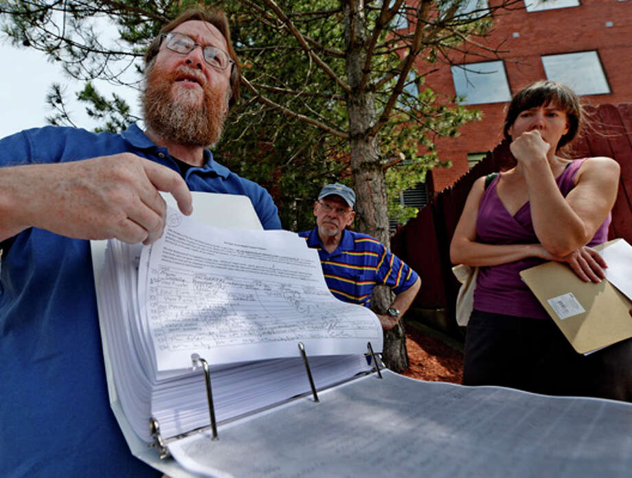 Jack Conway, left and Cara Benson, right, of Save East Greenbush show signatures against a casino coming to their town outside the state at the New York State Gaming building Monday morning June 30, 2014 in Schenectady, N.Y.    Today at 4 P.M. was the deadline for bids to hold a license for one of seven full service casinos  in New York State.   (Skip Dickstein / Times Union) Photo: SKIP DICKSTEIN, ALBANY TIMES UNION / 00027558A
