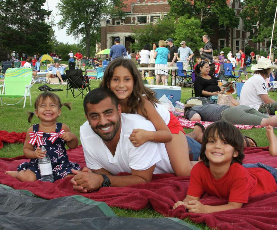 Mina, Sophia and Gian Karimnejad and their father, Garsy, smile at the 2012 New Canaan Family Fourth. Photo: Contributed Photo, ST / New Canaan News