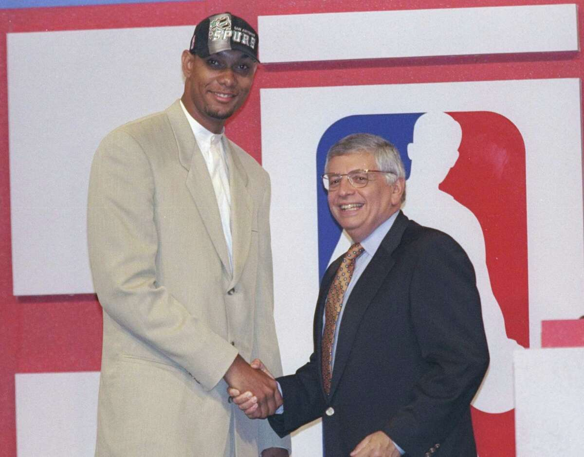 The classic Tim Duncan in a tan suit shakes hands with NBA Commissioner David Stern during the 1997 NBA Draft.