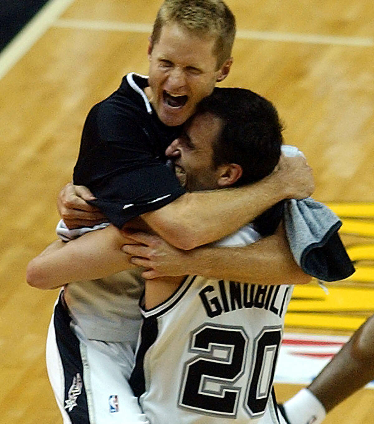 Steve Kerr jumps into Manu Ginobili's arms after Kerr won his second title with the Spurs.