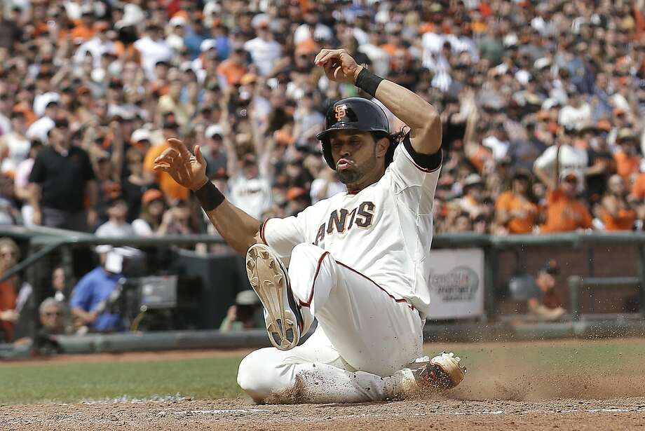 San Francisco Giants' Angel Pagan scores on Buster Posey's sacrifice fly against the Colorado Rockies during the seventh inning of a baseball game in San Francisco, Saturday, June 14, 2014. (AP Photo/Jeff Chiu) Photo: Jeff Chiu, Associated Press