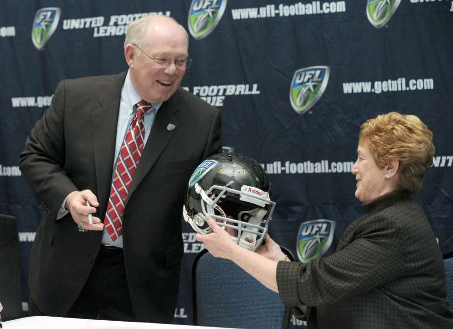 Chris Palmer, left, just named as head coach of the United Football League's Hartford team, presents Governor M. Jodi Rell with an autographed team helmet. Photo: Carol Kaliff / The News-Times