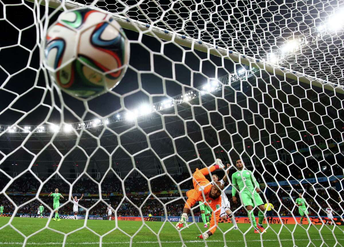 PORTO ALEGRE, BRAZIL - JUNE 30: Rais M'Bolhi of Algeria fails to save a shot by Andre Schuerrle of Germany (not pictured) for Germany's first goal in extra time during the 2014 FIFA World Cup Brazil Round of 16 match between Germany and Algeria at Estadio Beira-Rio on June 30, 2014 in Porto Alegre, Brazil.