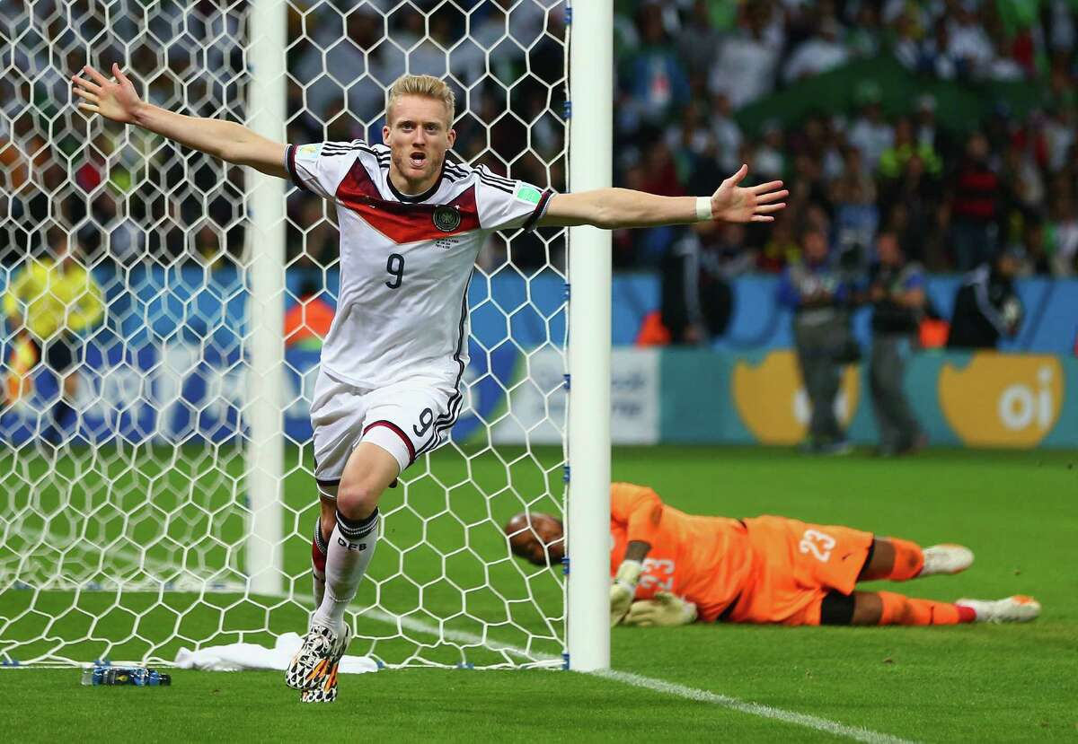 PORTO ALEGRE, BRAZIL - JUNE 30: Andre Schuerrle of Germany celebrates scoring his team's first goal in extra-time past goalkeeper Rais M'Bolhi of Algeria during the 2014 FIFA World Cup Brazil Round of 16 match between Germany and Algeria at Estadio Beira-Rio on June 30, 2014 in Porto Alegre, Brazil.
