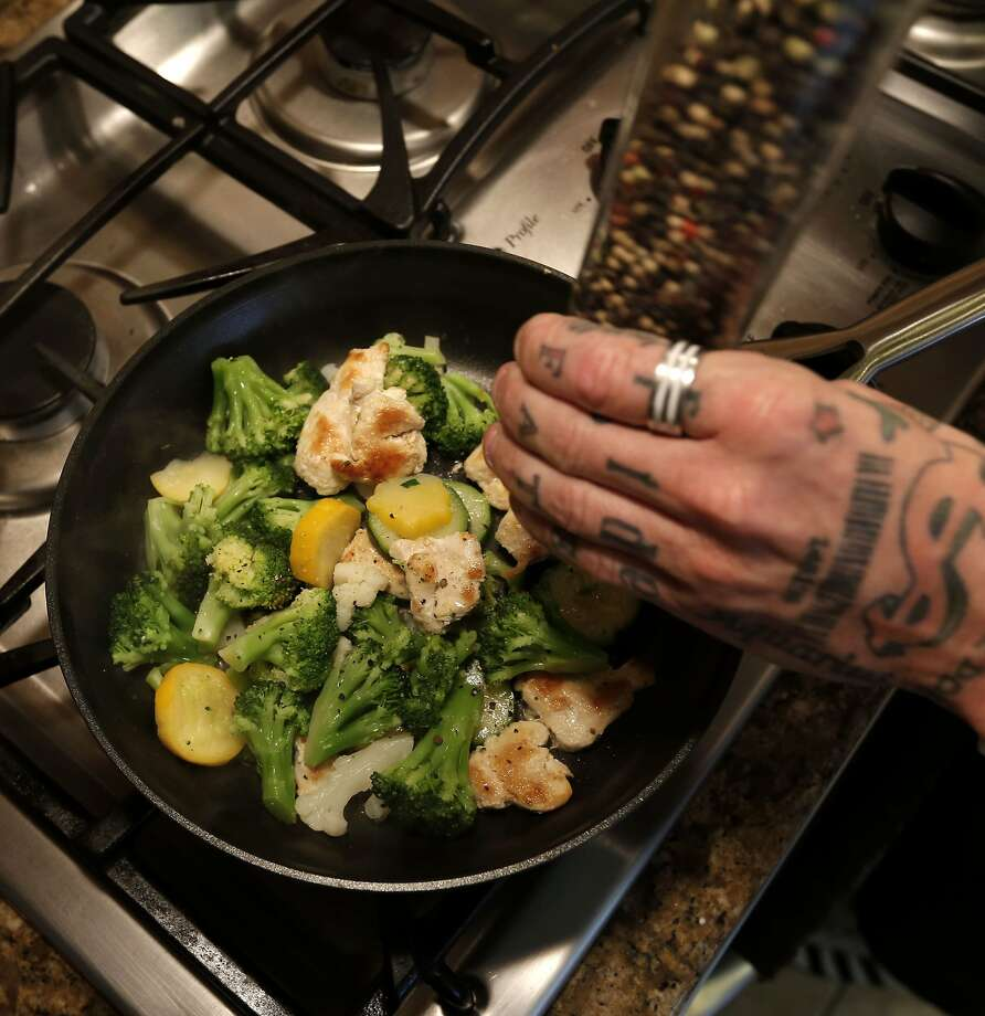 Jason Leite adds spices to his fasting meal which includes chicken, vegetables and nuts, which he prepares at his home in Mountain House, Calif. on Thursday June 5, 2014. Leite lost 60 pounds in one year by intermittent fasting, a dieting trend that was recently popularized in a book. He is now eating a healthy amount of food one day, then cutting down to about 500 calories on the other days. Photo: Michael Macor, The Chronicle