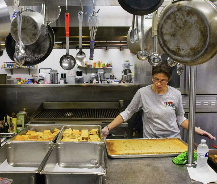 Ruby Lozano works on a pan of cornbread in the kitchen of the San Antonio Food Bank, which distributes all kinds of fresh and nonperishables to 430 partners in Bexar County. Photo: Photos By Ricardo Segovia / For The Northeast Herald