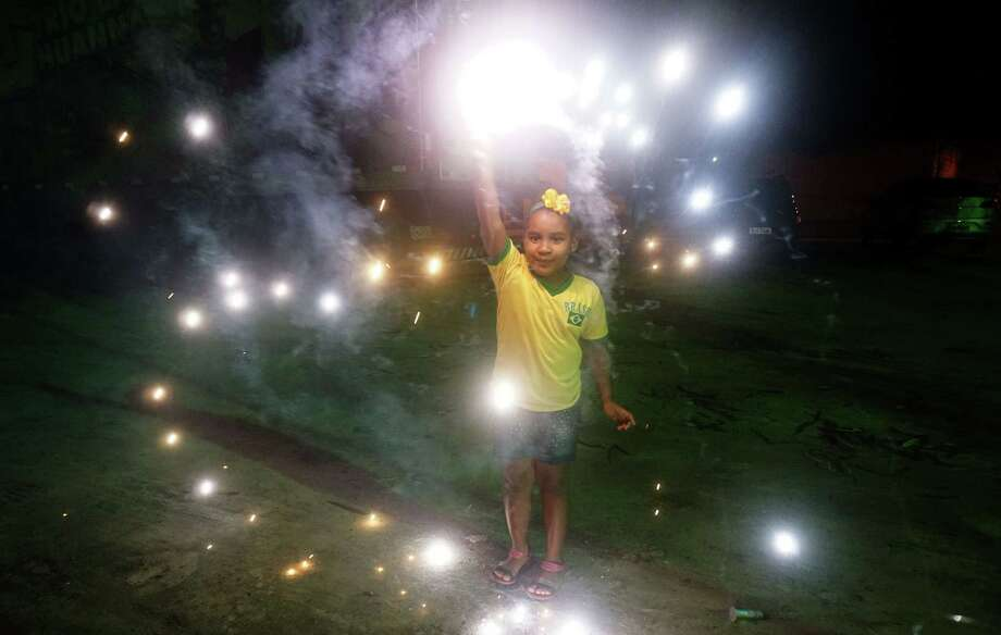 Safety experts say young children --  like this Brazilian celebrating after a World Cup match --  shouldn't play with fireworks. Photo: PATRIK STOLLARZ, Staff / AFP