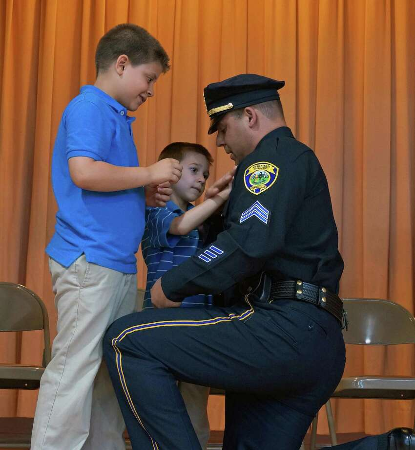 Edward and his younger brother, Zachary, help pin their father's new badge, as Ed Nook was promoted to sergeant in the Fairfield Police Department. Photo: Genevieve Reilly / Fairfield Citizen