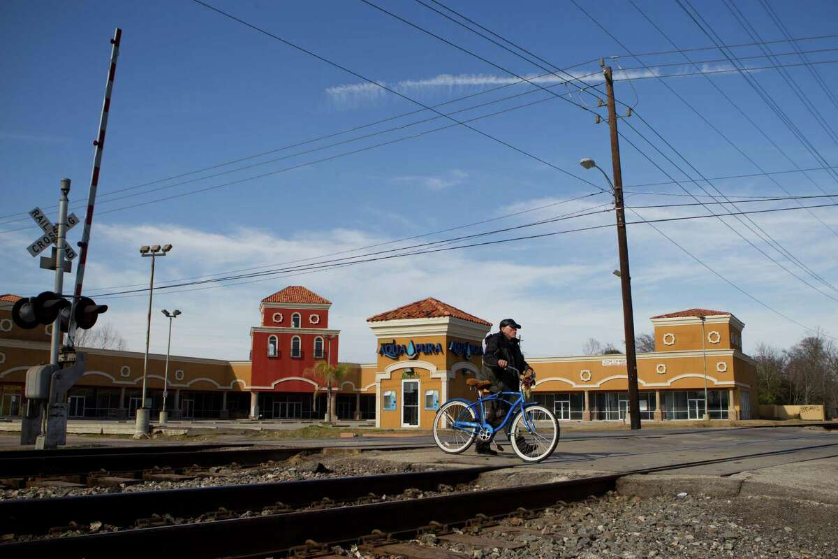 A cyclist walks his bicycle across the railroad tracks on Harrisburg near Hughes on Feb. 5. Metro was planning an underpass of the tracks, but since it discovered more contamination than expected in the area, it can't disturb the ground. Now it wants to build an overpass instead.