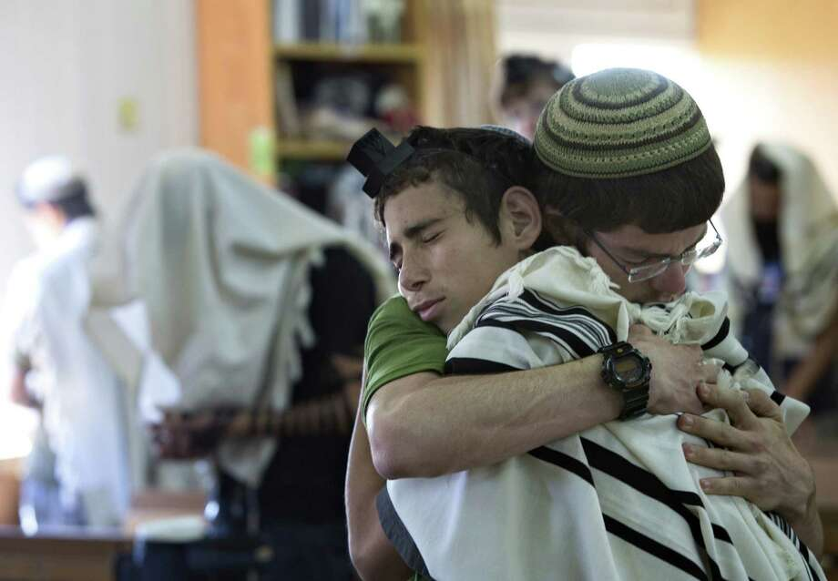 Two weeks before the three youths' bodies were found, religious students hugged at the synagogue in the Jewish settlement of Kfar Etzion, where two of the three missing Israeli teens studied. Photo: Sebastian Scheiner / Associated Press / AP