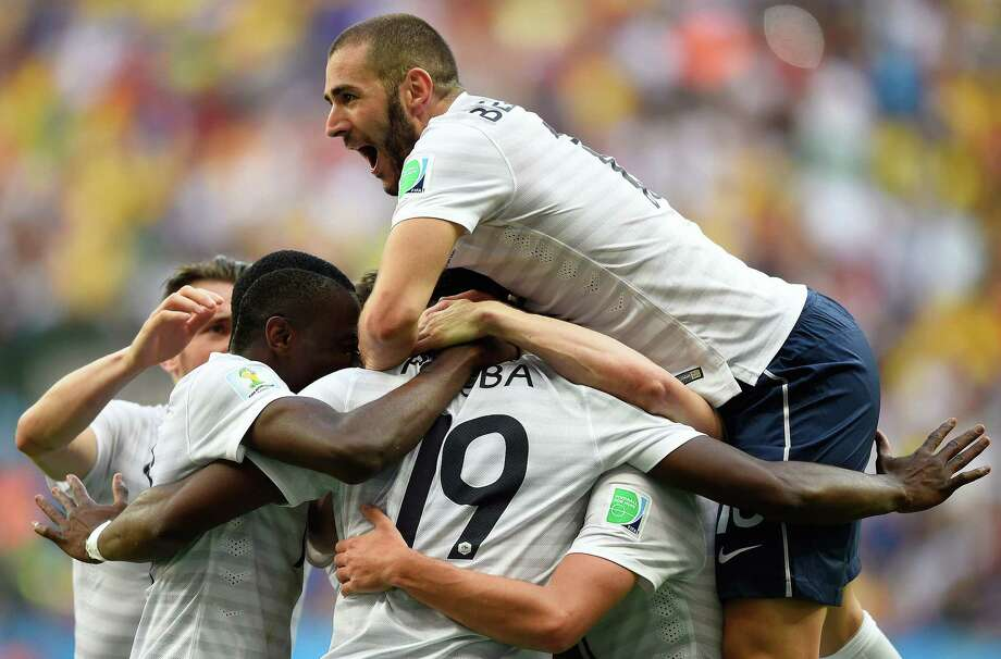 France midfielder Paul Pogba (19) celebrates with forward Karim Benzema (top) and other teammates after scoring the first goal late in a 2-0 round-of-16 victory over Nigeria. Photo: Fabrice Coffrini / AFP / Getty Images / AFP