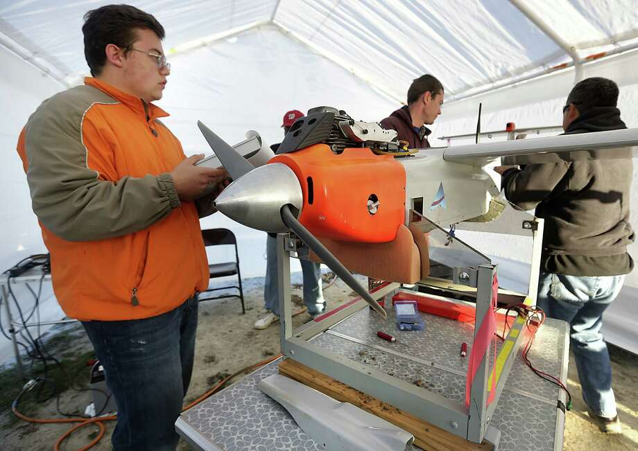 Martin Hass (left) and two other men perform a preflight check on a drone that Texas A&M University-Corpus Christi used in test flights over South Texas in January. Photo: Bob Owen / San Antonio Express-News / ©2013 San Antonio Express-News