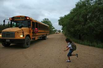 Vanessa, daughter of Judy Vargas, runs for the school bus as a truck approaches behind it.<br /><br /> In La Salle County, which includes Gardendale, 39 percent of children live in poverty.