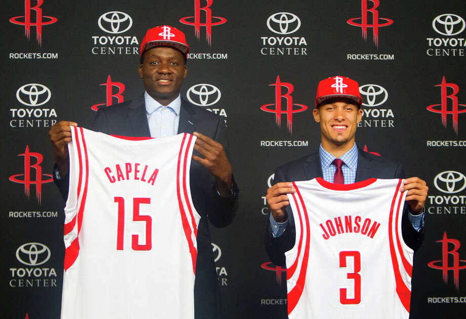 Rockets draft picks Clint Capela, left, and Nick Johnson put their faces behind their jerseys as they meet the media at Toyota Center on Monday. Photo: Cody Duty, Staff / © 2014 Houston Chronicle